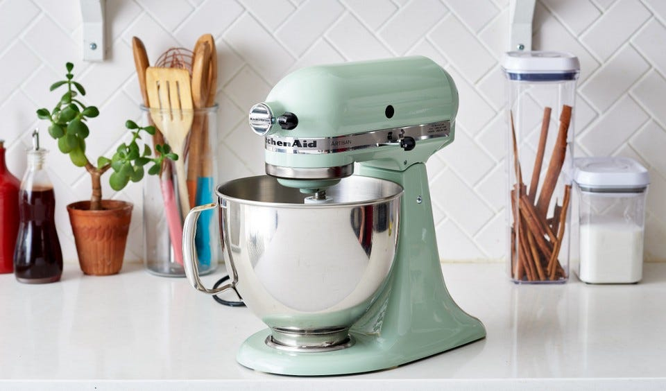 a shiny sea foam green kitchen aid mixer on a white countertop