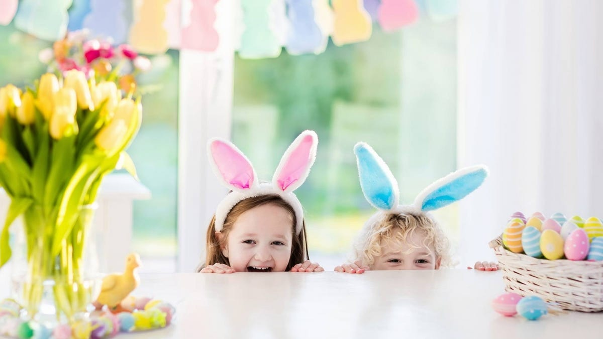 Two children wearing bunny ears peeking from behind a counter-top with a basket full of colorful Easter eggs sitting on it.