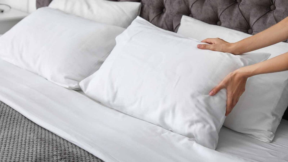 Woman's hands placing a pillow on a bed.
