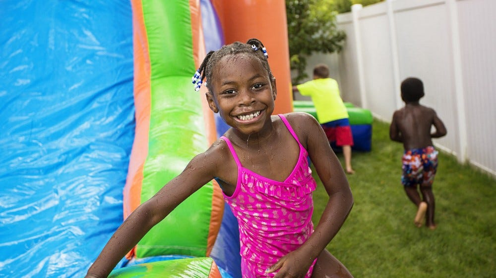 A young girl smiling and standing next to a backyard waterslide.