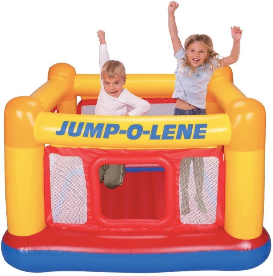 Two kids jumping in small bounce house.