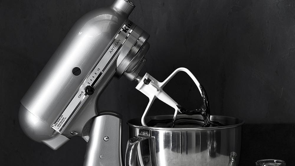 A stainless steel kitchenaid mixers sits on top of a counter against a black background