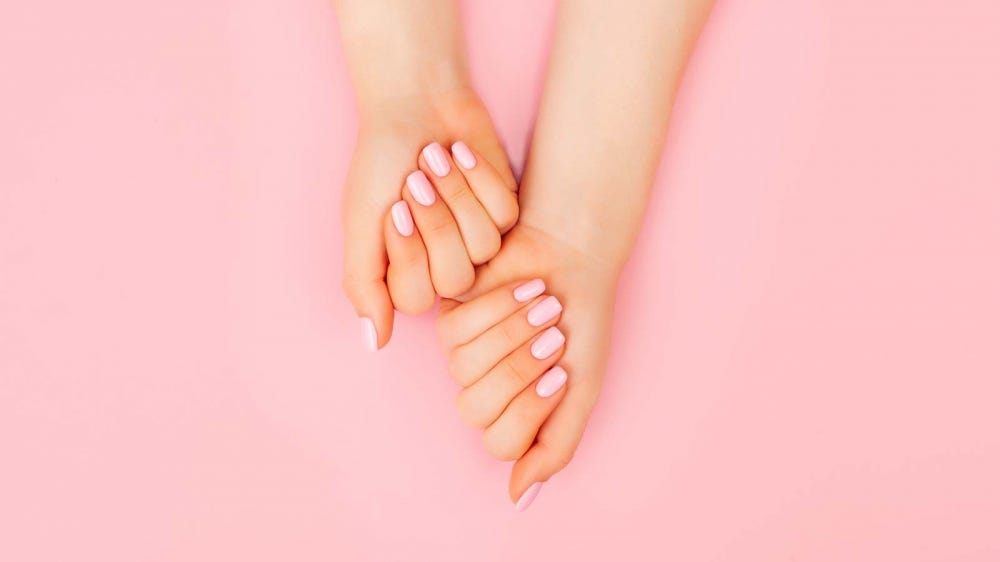 A pair of hands with soft pink press on nails against a pink background.
