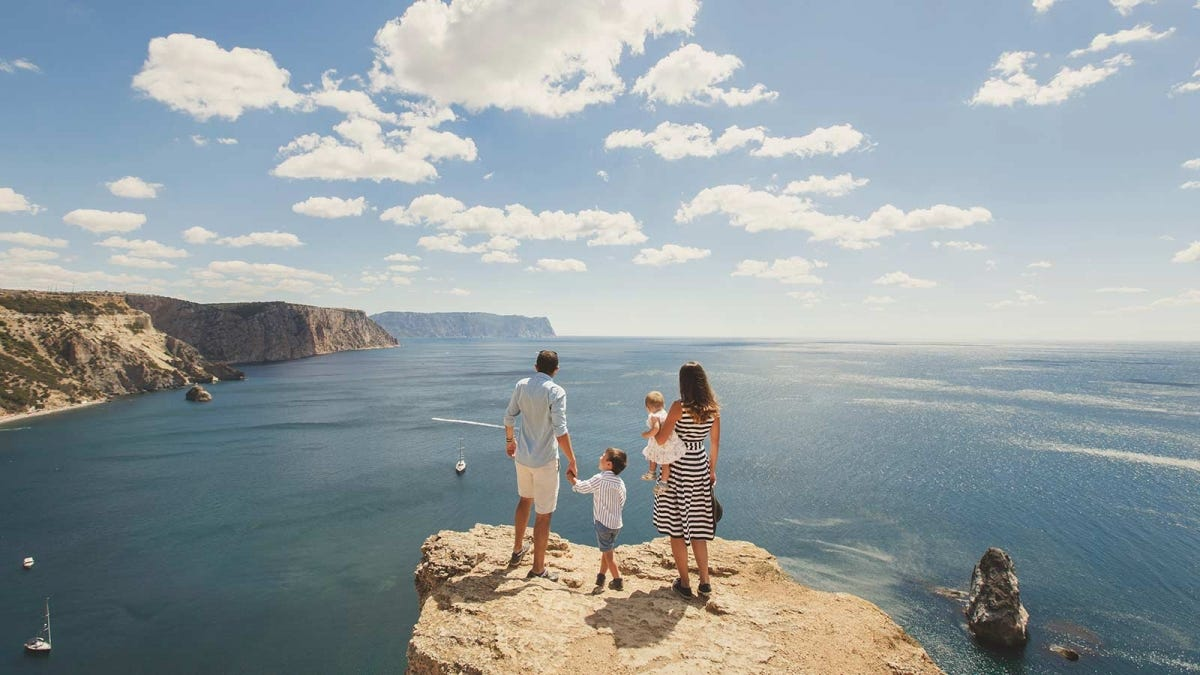 A family standing on a large rock that extends into the sea .