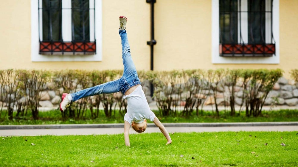 A young girl doing a cartwheel on some grass.