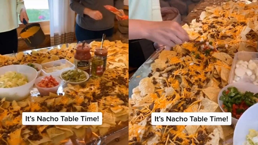 A table covered in tin foil and piled high with nachos and various condiments.