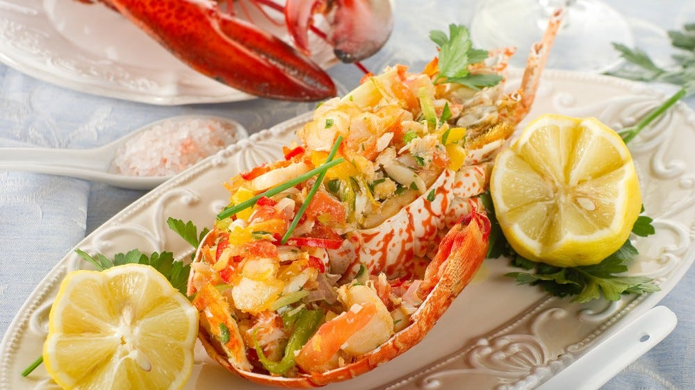 A fancy lobster dinner prepared on a porcelain serving dish.