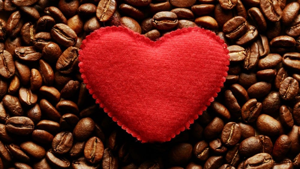 A red heart sitting on a pile of coffee beans.