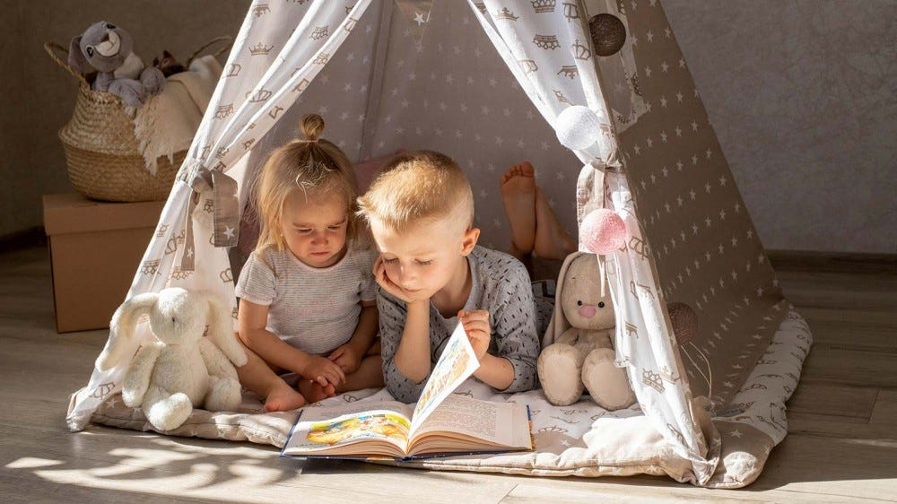 A little boy and girl reading a book in an indoor tent.