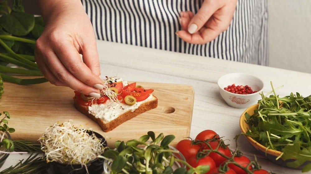 A woman making a vegetarian sandwich with micro greens, olives, and vegetables.