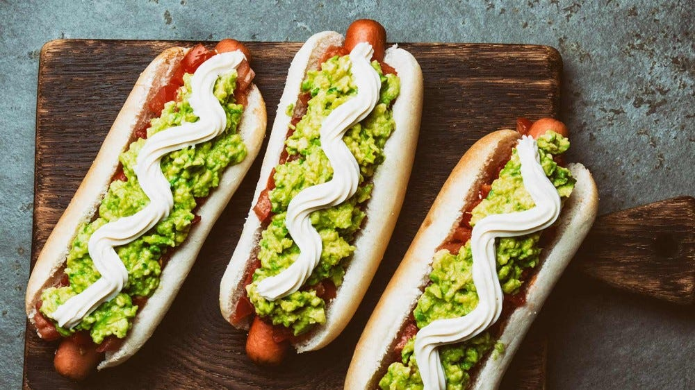 A hotdog topped with guacamole and sour cream.