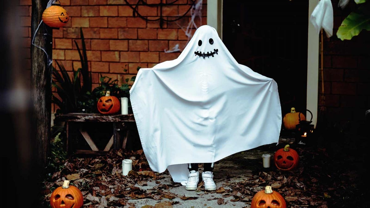 child standing in front of a house dressed up for Halloween in a homemade ghost costume