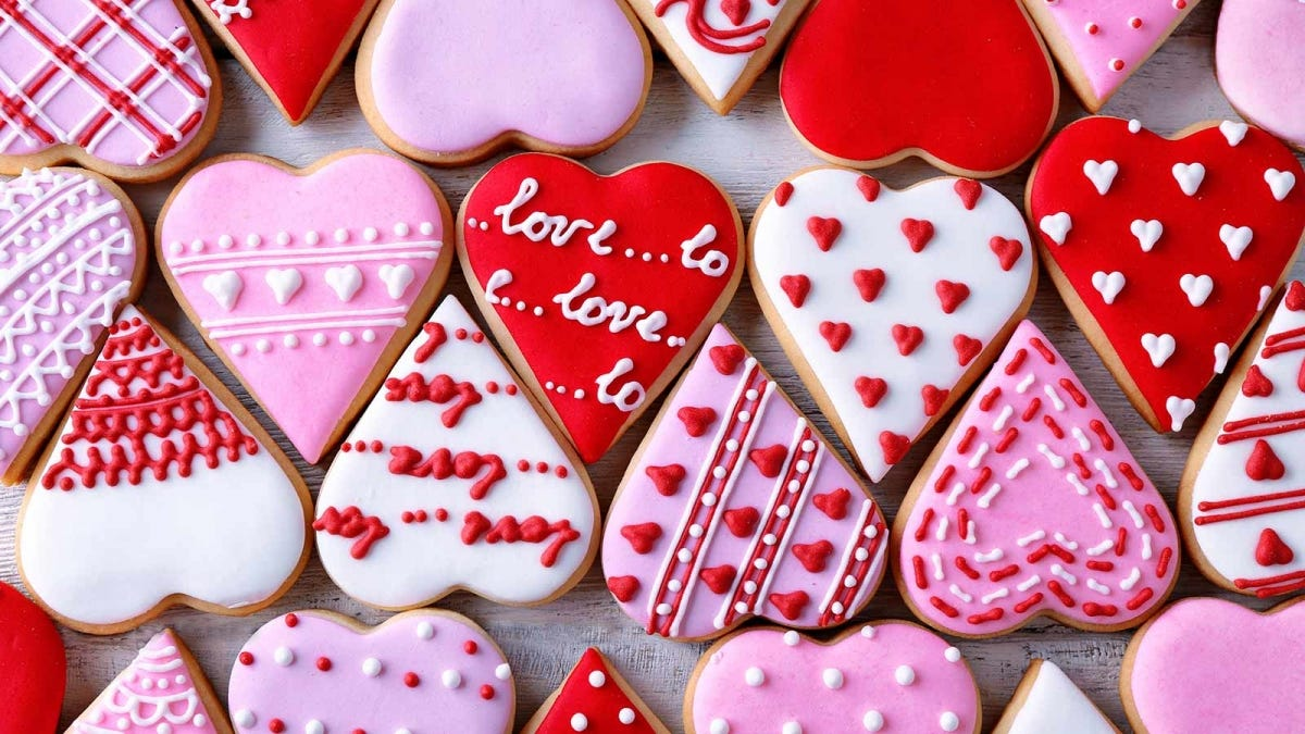 Heart-shaped cookies with white, red, and pink frosting.