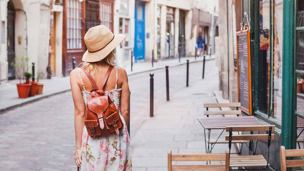 A woman in a sundress, exploring the streets of a new city she's visiting