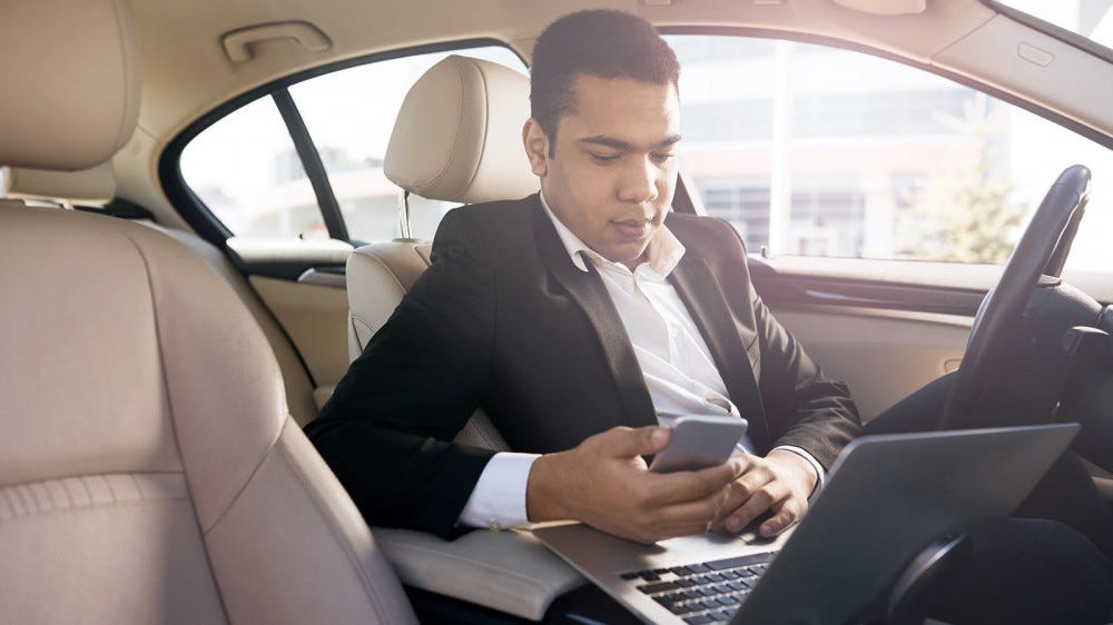 A businessman working in his car, using the center console as a laptop desk.