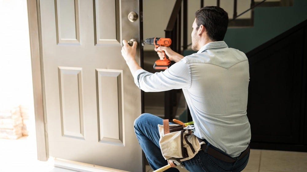 Man fixing a loose door knob at his dad's house.