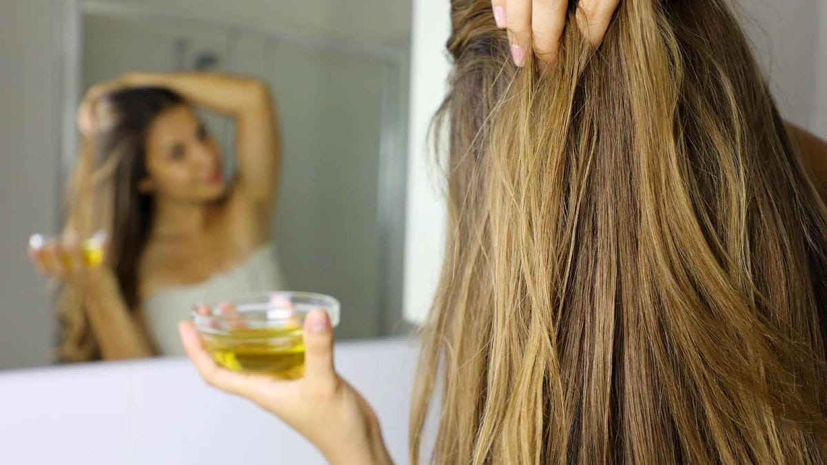 A woman holding a dish of oil while she looks in the mirror.