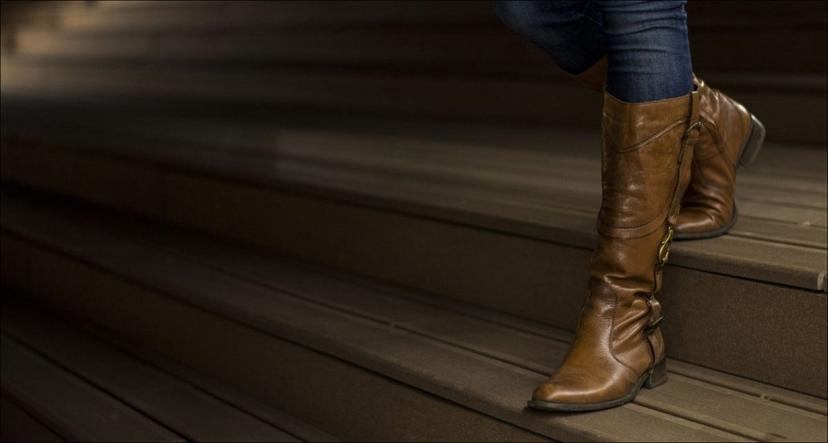 Closeup of woman's leather boots on wooden stairs