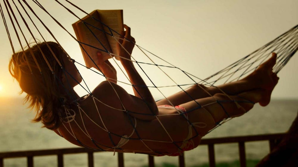 A young woman reading a book in a hammock by the ocean.
