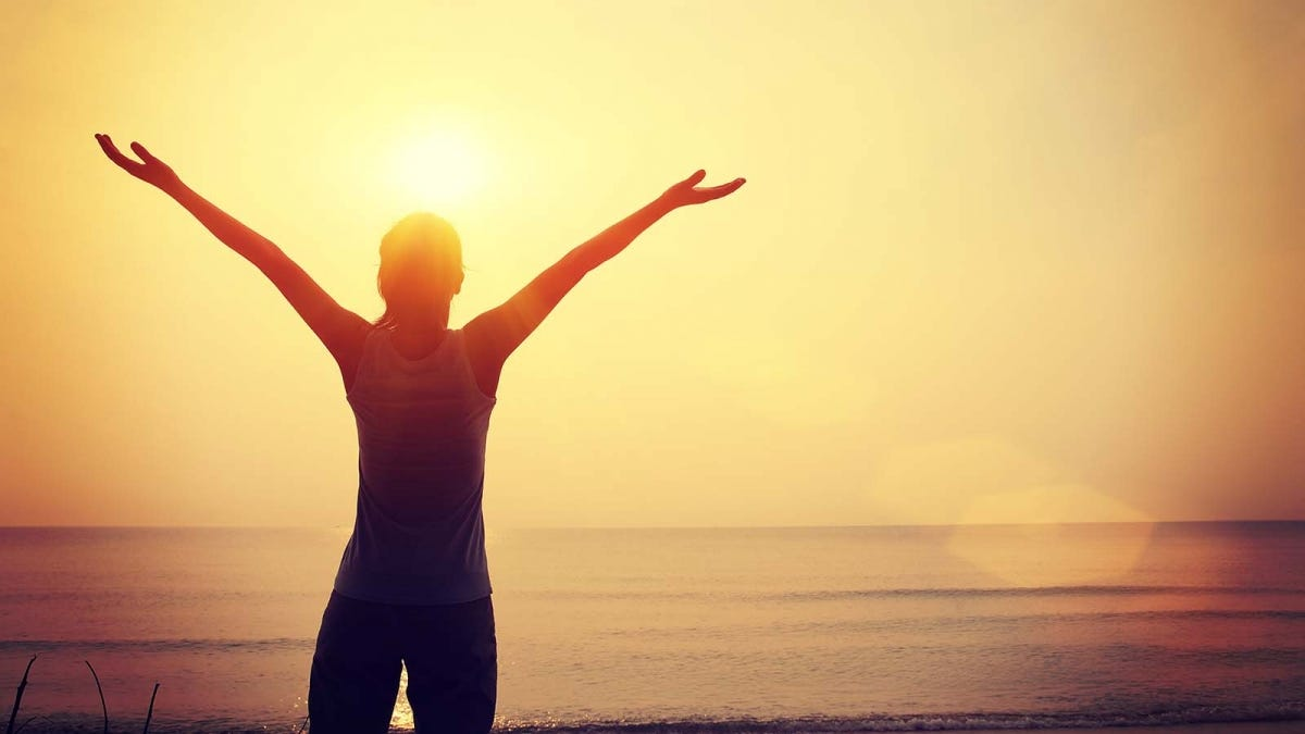 Woman confidently raising her arms at sunrise in front of the ocean