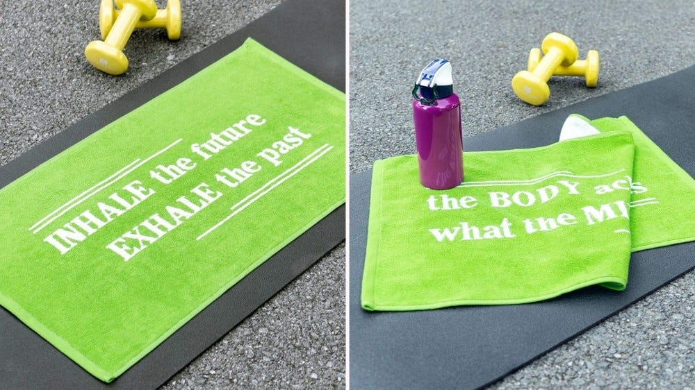 Two Luzia yoga towels featuring motivational sayings.
