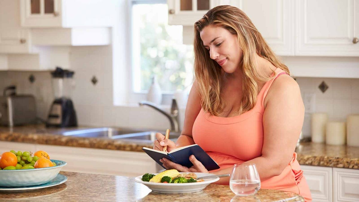 woman tracking her food intake using a journal in a sunny kitchen