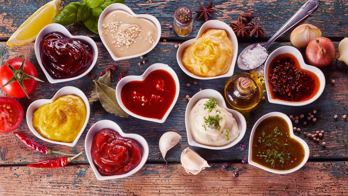 Various condiments in heart-shaped bowls on a rustic wooden table.