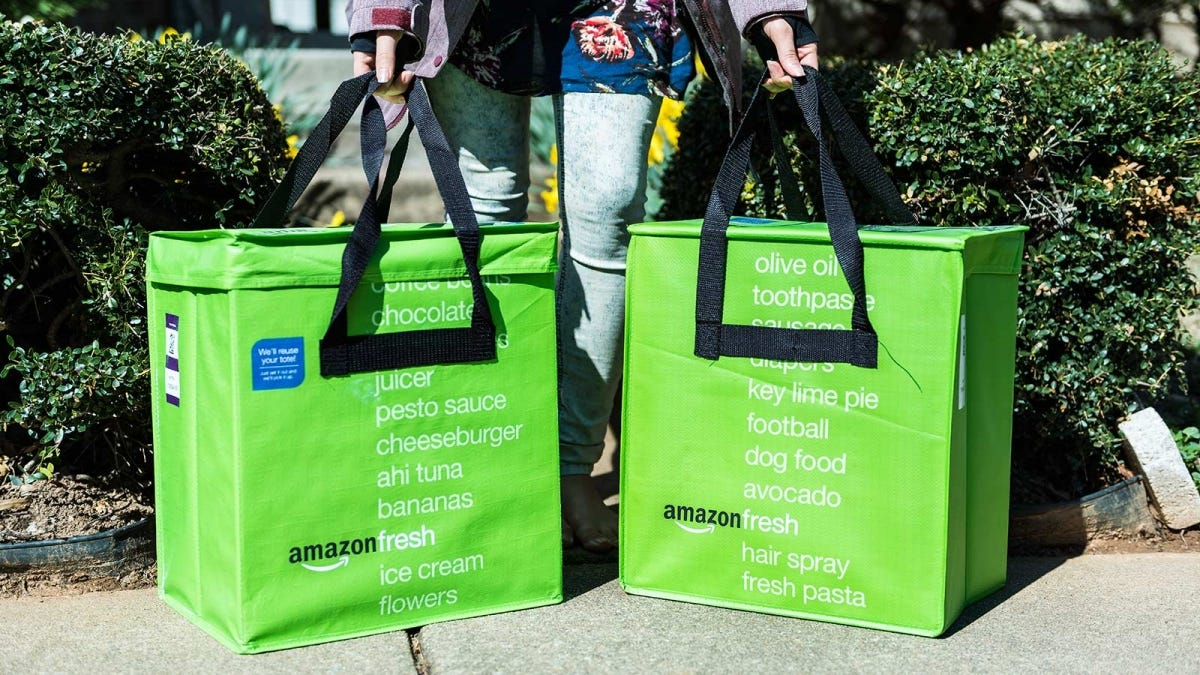 A woman's hands picking up two Amazon Fresh bags from the curb.