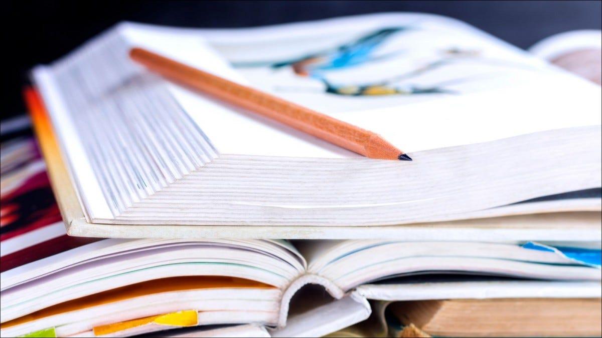 pile of textbooks open on desk