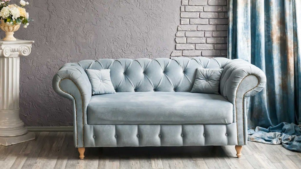 A gray-blue Chesterfield sofa in a sunny room.