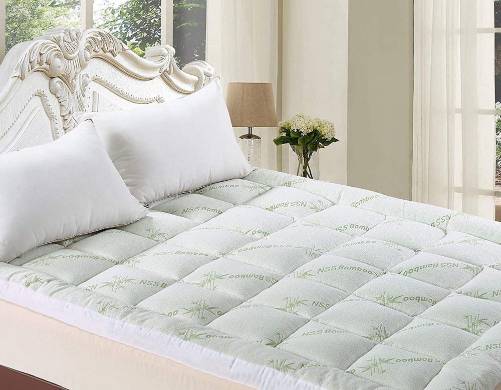 Bed with an ornate white headboard and a pillowed mattress topper
