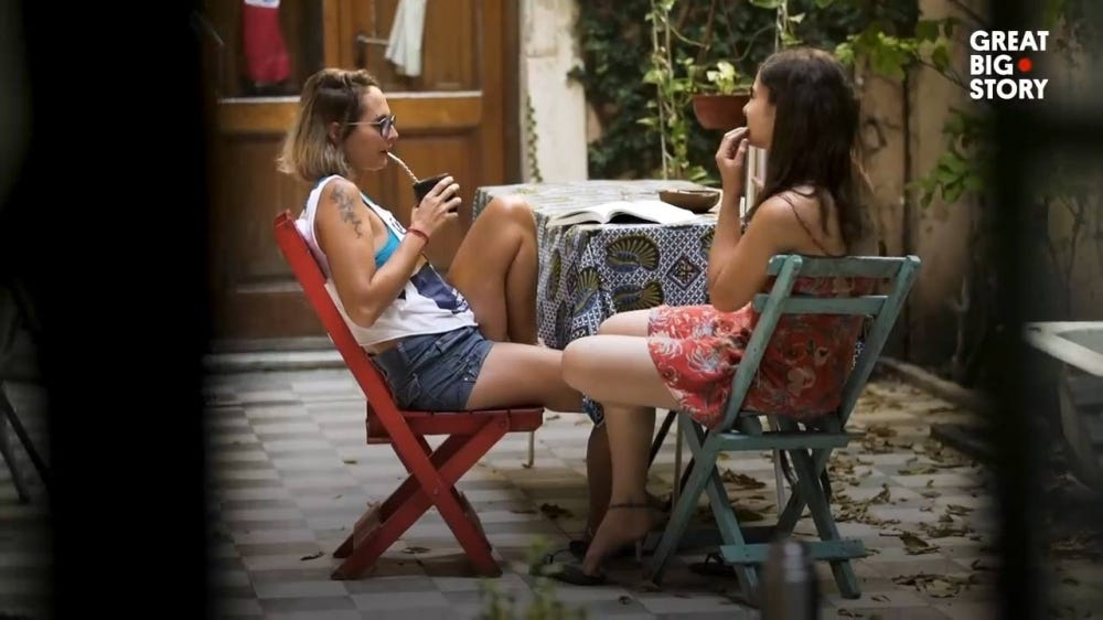 Two young women drinking mate tea in a courtyard.