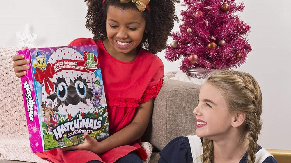 Two young girls looking at the box for Hatchimal's Advent calendar.