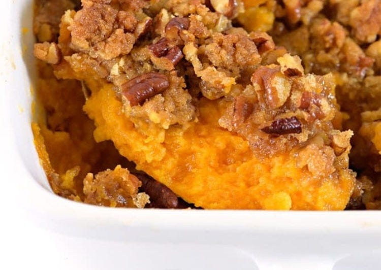 A bright and beautiful sweet potato casserole being scooped.