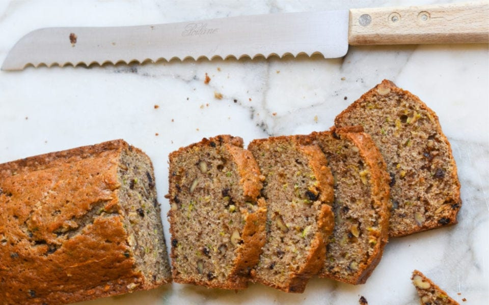 Four slices of zucchini bread, with a bread knife nearby.
