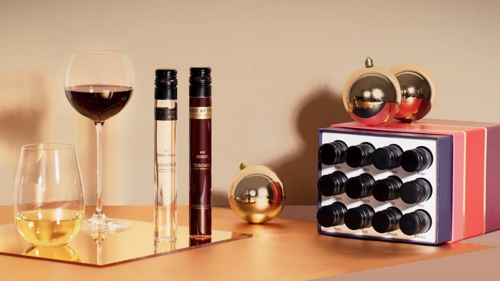 Two glasses and two bottles of wine sit next to a wine Advent calendar.