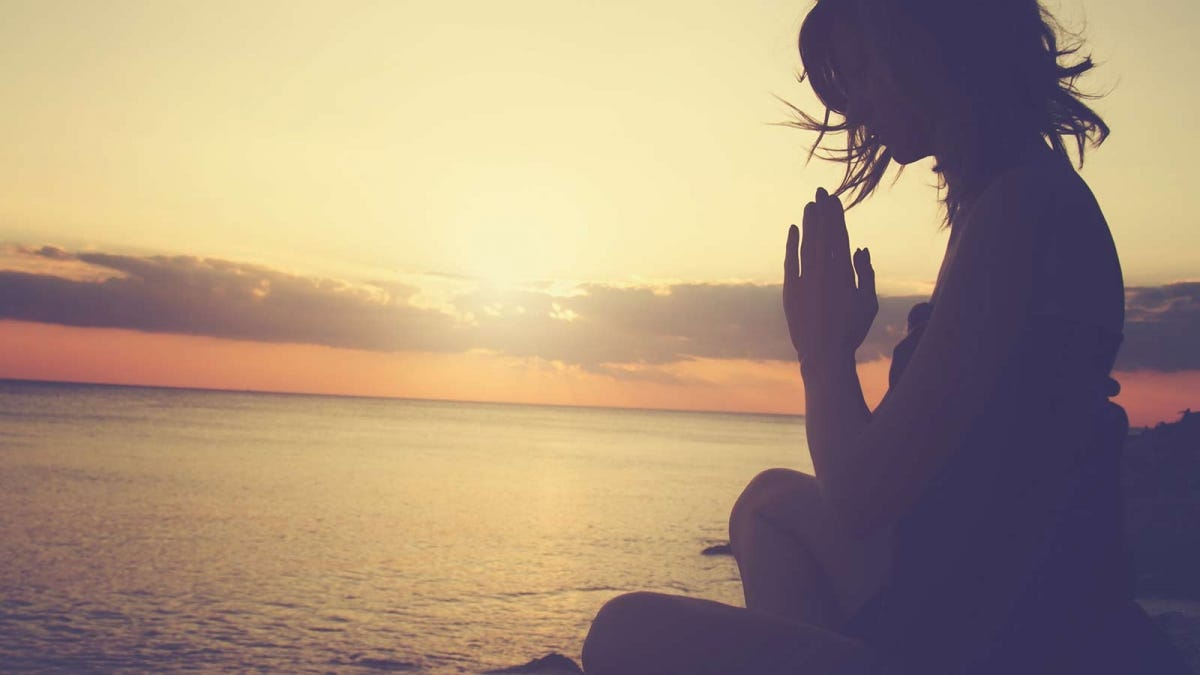Woman meditating at sunset beside a body of water.
