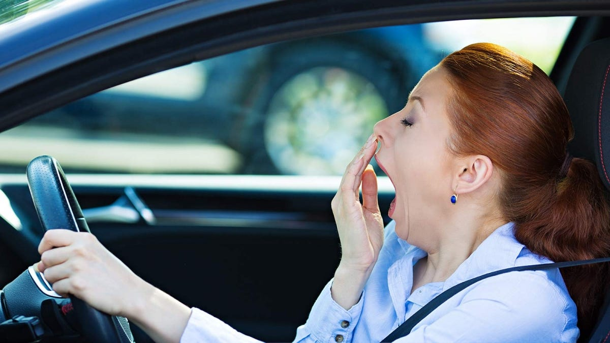 Woman yawning in her car on the way to work.