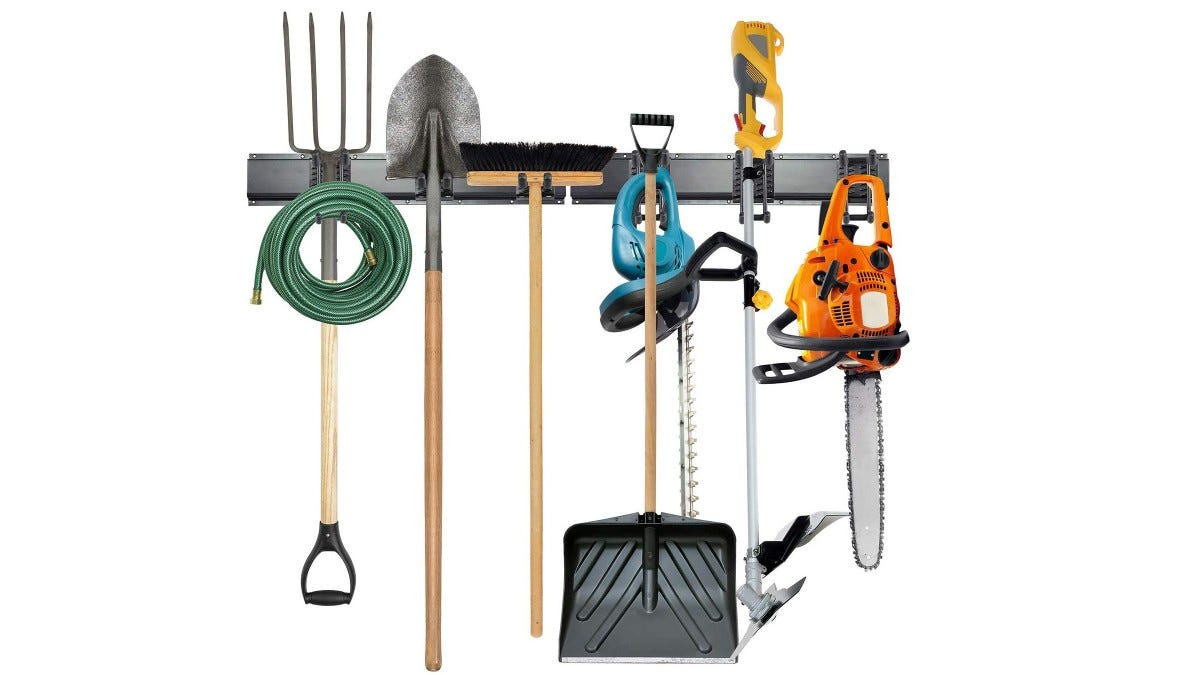 An Eight-Piece Tool Storage Rack holding a pitchfork, hose, two shovels, a shop broom, an electric sander, and a chain saw.