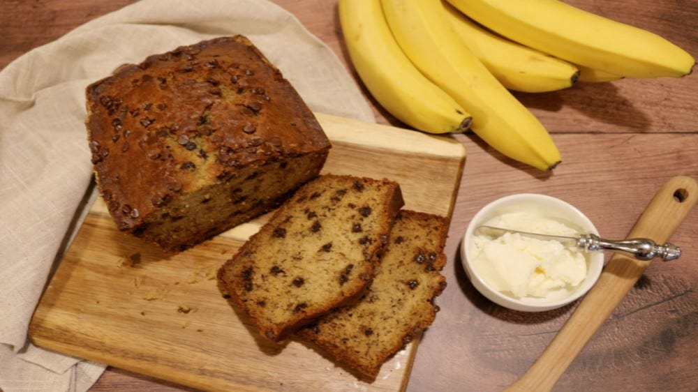 A loaf of banana bread on a cutting board, next to a bunch of bananas, and a bowl of spreadable butter.