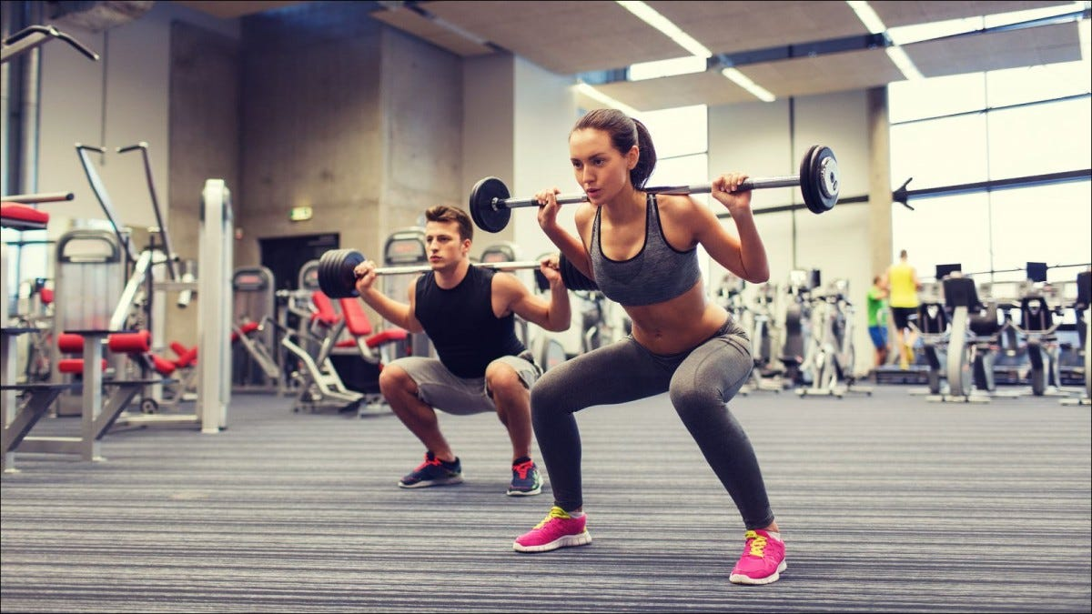 young man and woman with barbells doing shoulder press squats in gym