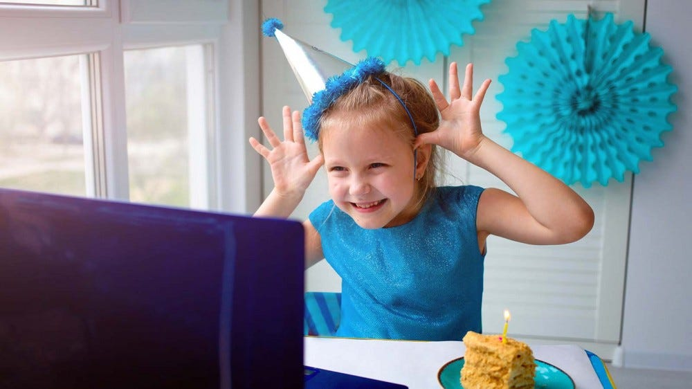 A little girl making a silly face at a laptop screen during a virtual birthday party.