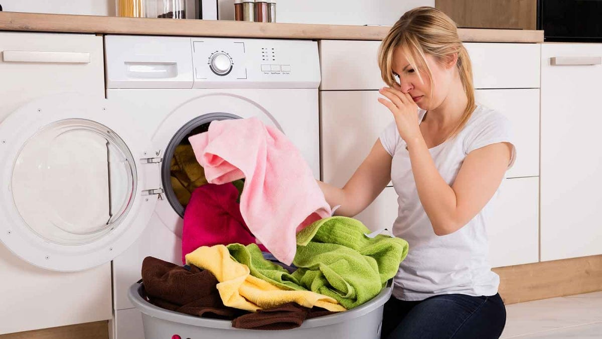 woman frowning while smelling her unsanitized laundry