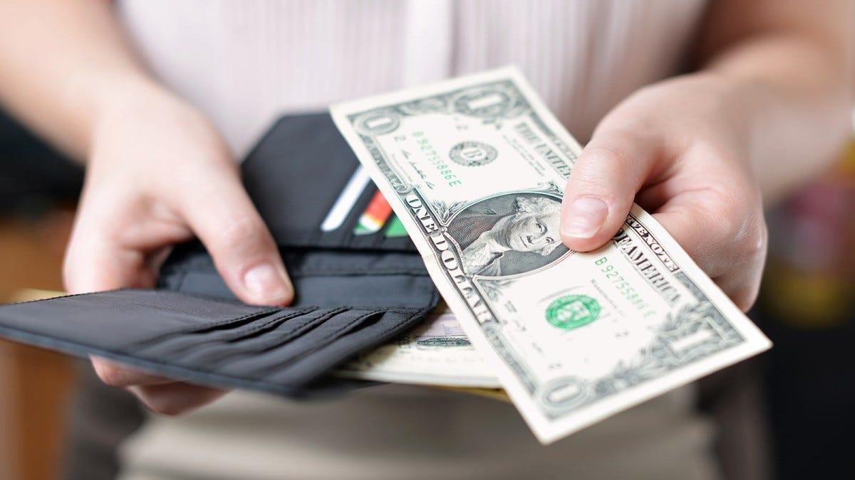 A woman's hands holding an open wallet and a one-dollar bill.
