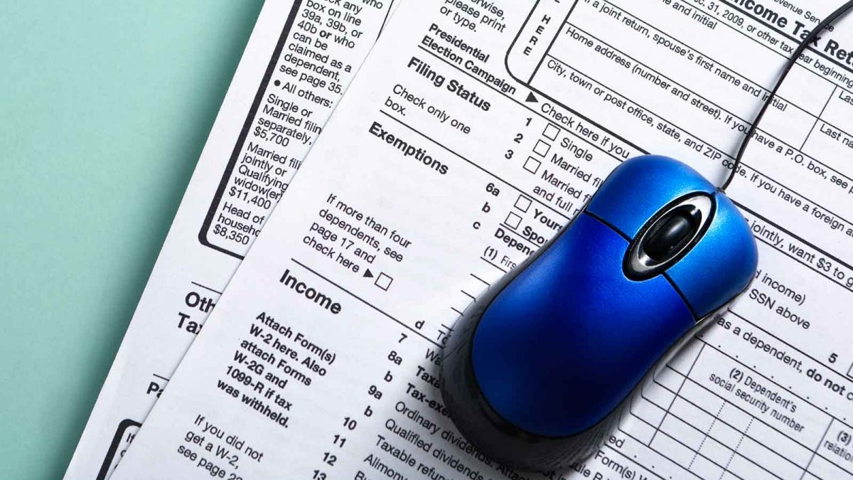 A computer mouse resting on tax forms.