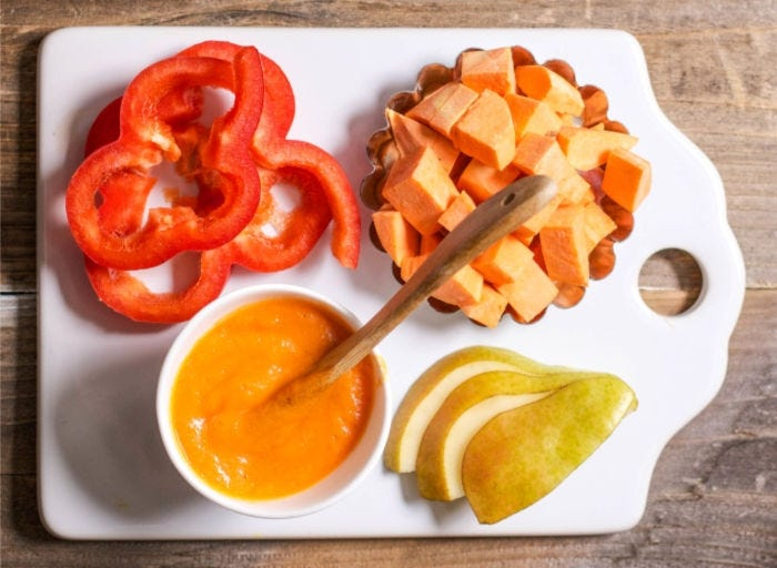Sliced red bell pepper, cubed sweet potato, and sliced pears with a bowl of baby food