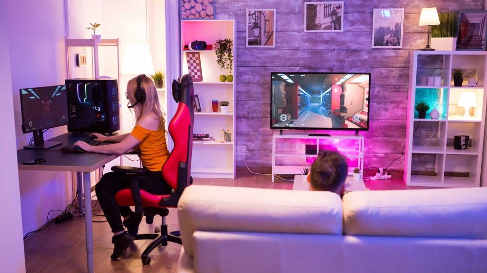 A couple playing video games in a living room lit by smart lights.