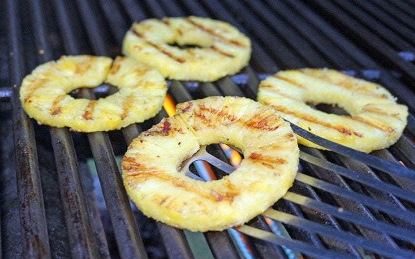Grilling pineapple and using a fish spatula to flip the delicate fruit rings.