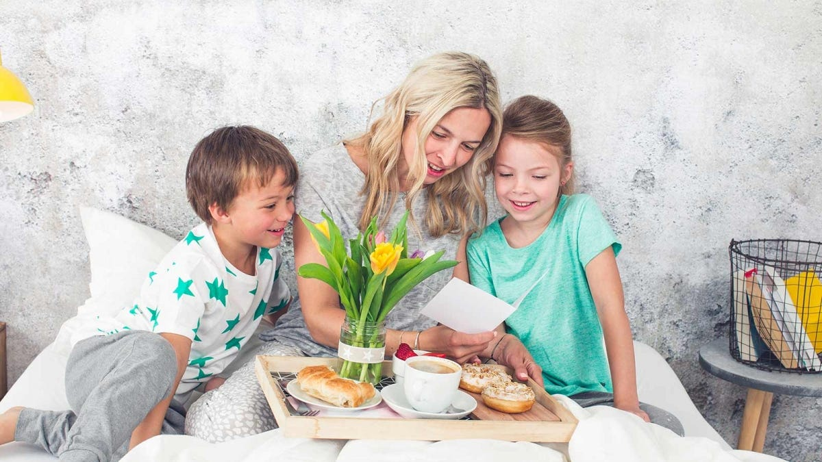 A mother eating breakfast in bed reading a Mother's Day card with her children.