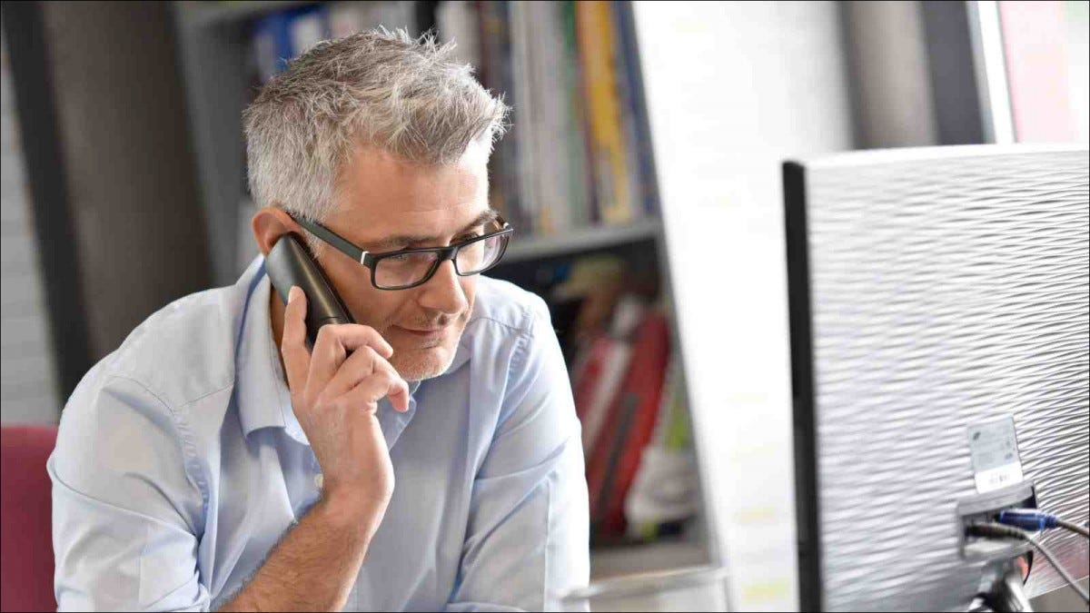 man in home office talking on phone